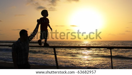 silhouettes of father and son on sunset sea background - stock photo