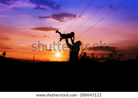 silhouettes of father and son play at mountain range and high voltage electricity pylon sunset background - stock photo