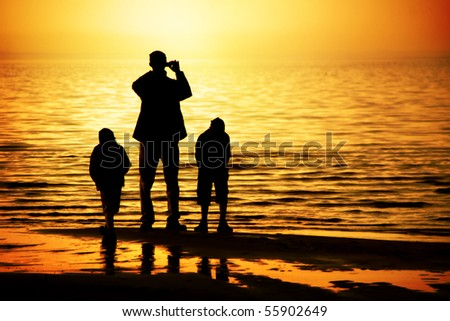 Silhouettes of father and two sons by the ocean looking to the sunset - stock photo