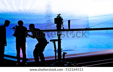 Silhouettes of film crew in front of  blue lighted stage. Selective focus.  - stock photo