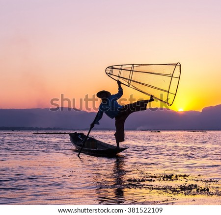 Silhouettes of fisherman and his famous fishing pose with bamboo net on one leg on boat in Inle lake at evening sunset, Shan state, Myanmar  - stock photo