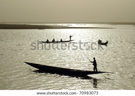 Silhouettes of fishermen in West Africa - stock photo
