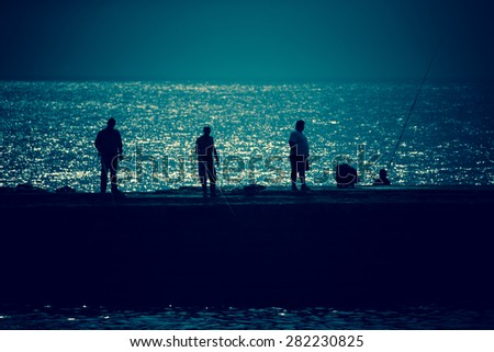 Silhouettes of fishermen on the pier in the background of the Atlantic Ocean. Toned.