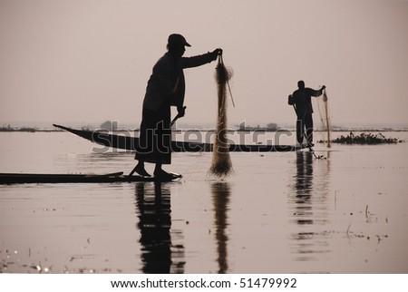 silhouettes of fishermen with sunrise at Inle lake, Myanmar, Burma, Asia - stock photo
