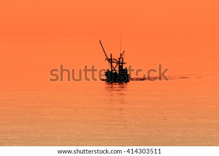 Silhouettes of fishing boats with orange light . - stock photo