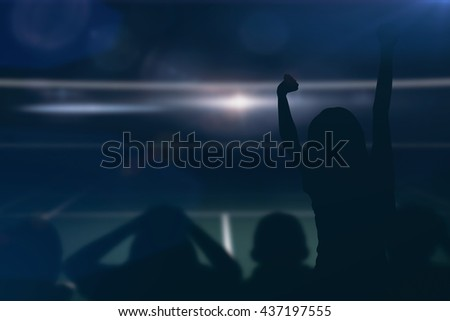 Silhouettes of football supporters against view of a tennis field - stock photo