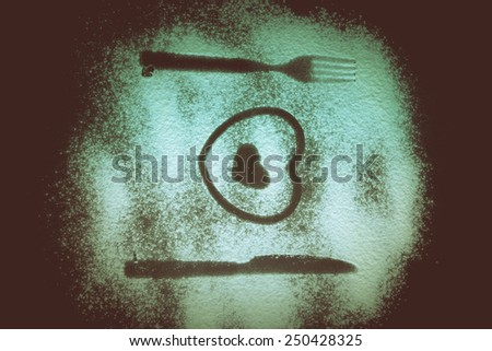 Silhouettes of fork, knife and hearts on the flour on a black background. Toned.