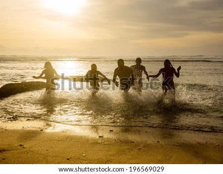 Silhouettes of group friends running out of the ocean on the beach during sunset - stock photo