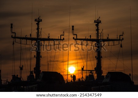 silhouettes of guard ships against the sunset  - stock photo