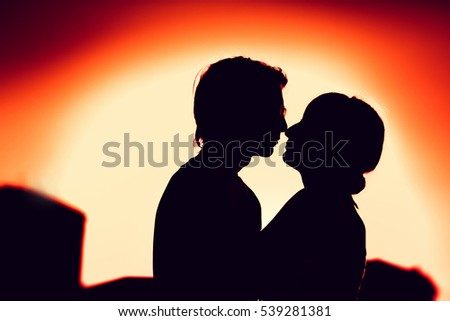 silhouettes of guy and the girl embracing on a background of the city.