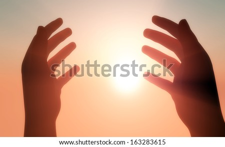 Silhouettes of hands in the sunshine. - stock photo
