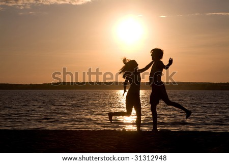 Silhouettes of happy couple having fun and laughing during summer vacations - stock photo