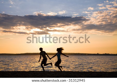 Silhouettes of happy couple running on seashore during summer vacations - stock photo