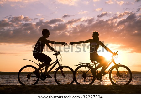 Silhouettes of happy couple stretching arms to each other while riding bicycles on seashore at sunset - stock photo