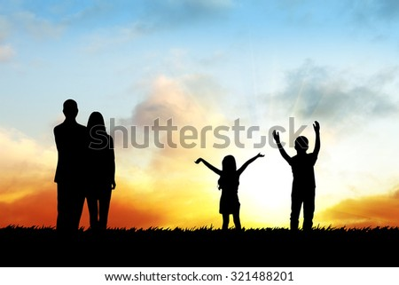 Silhouettes of happy family during sunset time