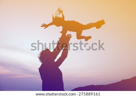 Silhouettes of happy family of father and daughter are having fun on sunset background. Father throws up daughter - stock photo