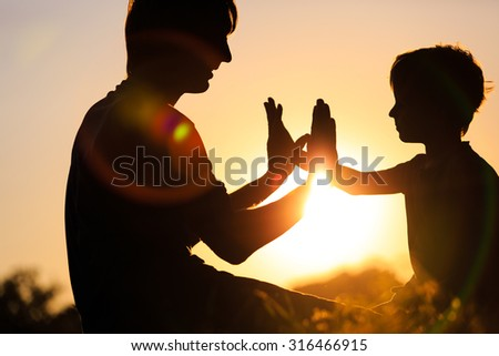 silhouettes of happy father and little son playing at sunset