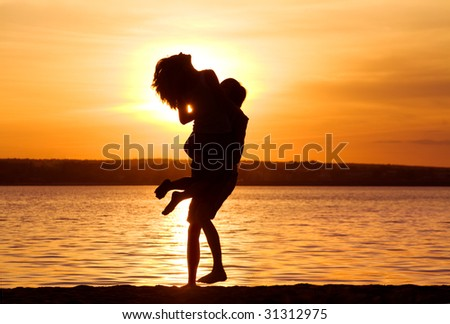 Silhouettes of happy guy holding his girlfriend by the lake at sunset - stock photo