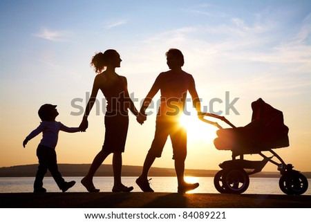 Silhouettes of happy parents walking with child and baby's stroller on the seacoast - stock photo