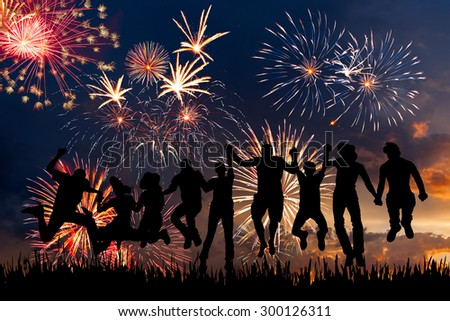 Silhouettes of happy people on a background fireworks in honor of holiday