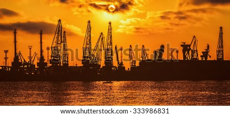 Silhouettes of Harbour Cranes in the Port at Sunset - stock photo