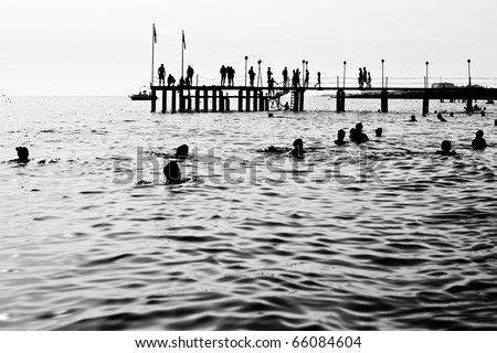 Silhouettes of having a rest people. It is black a white photo of a sea pier and having a rest people. - stock photo