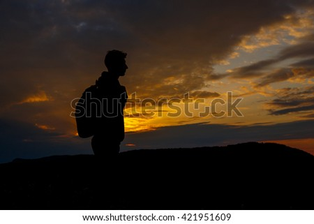 Silhouettes of hiker with backpack enjoying sunset view from top of a mountain. Winner silhouette on the mountain top. Sport and active life concept