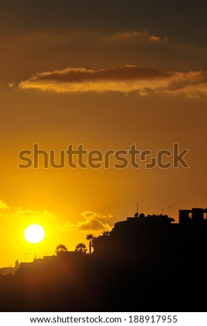 Silhouettes of Houses at Sunset over a Sea Village
