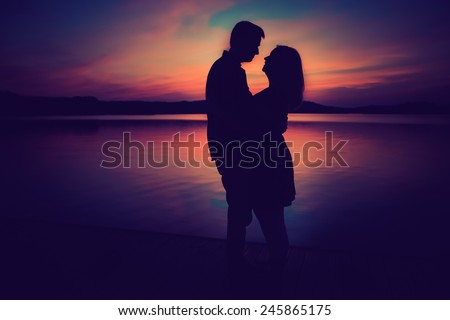 Silhouettes of hugging couple against the lake at sunset. Vintage photo. - stock photo
