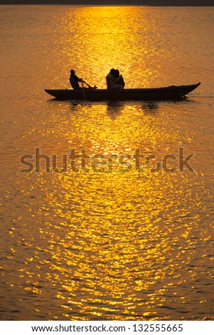 Silhouettes of Indian tourists take a sunset rowboat ride on the Ganges river in Varanasi, India - stock photo