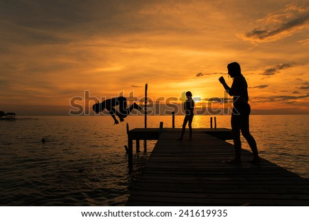 Silhouettes of kids jump into sea from pier.Summer travel in Phuket Thailand. - stock photo