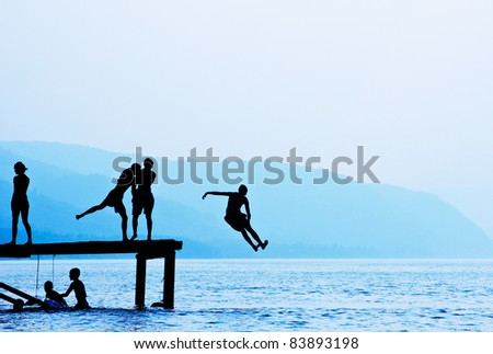 Silhouettes of kids who jump off dock on the lake.Blue toned. - stock photo