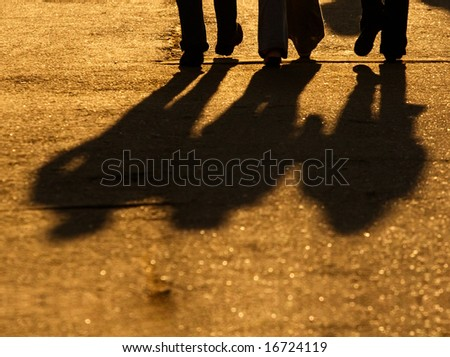 Silhouettes of legs of three walking friends - stock photo