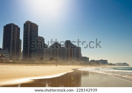 Silhouettes of Luxury Condominium Apartment Buildings by Sunrise in Barra da Tijuca Beach, Rio de Janeiro, Brazil - stock photo