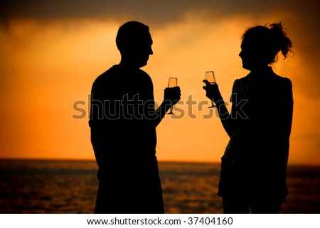 Silhouettes of man and woman with glasses on sea sunset - stock photo