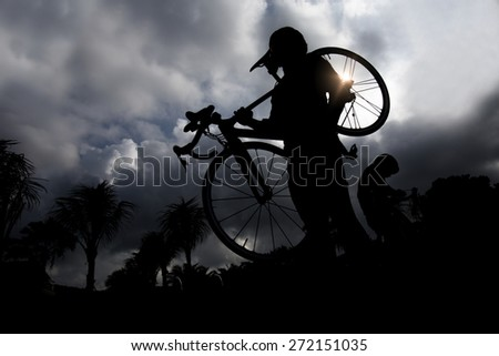 Silhouettes of man carrying  bike while walking at sunset - stock photo