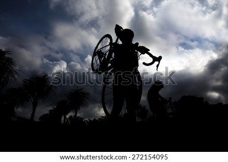 Silhouettes of man carrying  bike while walking at sunset