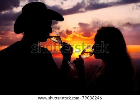 Silhouettes of Man in cowboy hat and woman drinking champagne from wine glasses at sunset dramatic sky background - stock photo