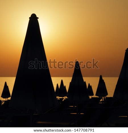 silhouettes of many closed  beach umbrellas on the beach on sunset time, Italy,Europe - stock photo