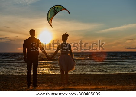 Silhouettes of men and women in the lush short skirt, reaching into the distance on the sand against the sea, the gold of sunset and a flying kite - stock photo