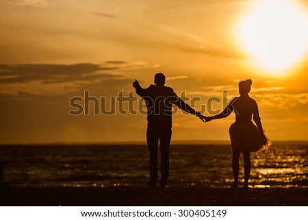 Silhouettes of men and women in the lush short skirt, reaching into the distance on the sand against the sea and the Golden sunset