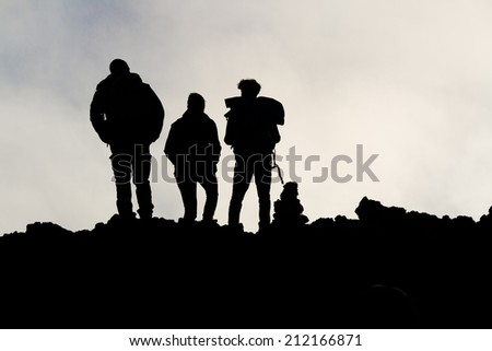 silhouettes of men on the volcano Etna - stock photo