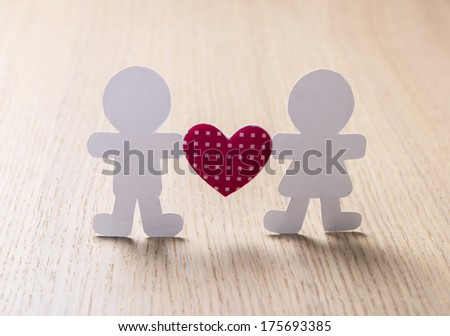 Silhouettes of men, women and heart cut out of paper on a wooden background. Happy couple in love. - stock photo