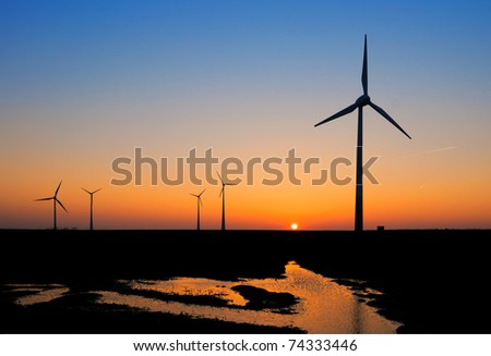 Silhouettes of modern windmills against sunset - stock photo