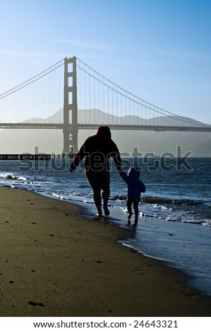 Silhouettes of mom and an infant daughter walking barefoot to silhouetted Golden Gate Bridge on a sunny but cold spring day. - stock photo