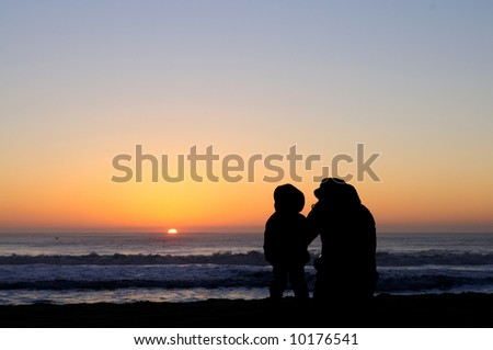 Silhouettes of mother and a toddler chatting and watching Pacific sunset. - stock photo
