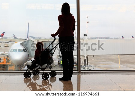 silhouettes of mother and baby in the airport - stock photo