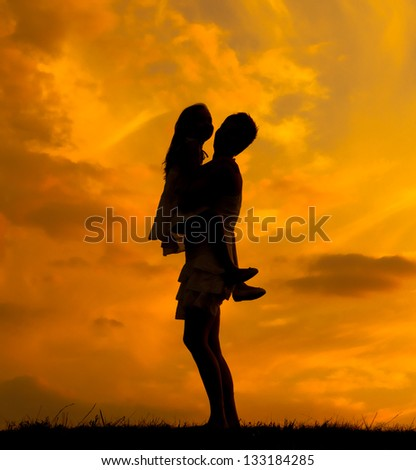 Silhouettes of mother and daughter hugging on beautiful spring day. - stock photo