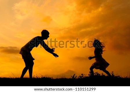 Silhouettes of mother and daughter meeting on the meadow at summer sunset. - stock photo