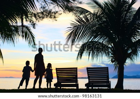 Silhouettes of mother and two kids at sunset on tropical island - stock photo